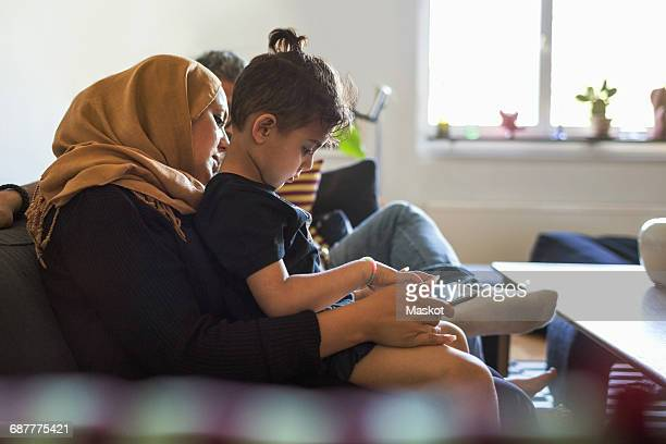 Side view of mother and son using digital tablet while sitting on sofa at home