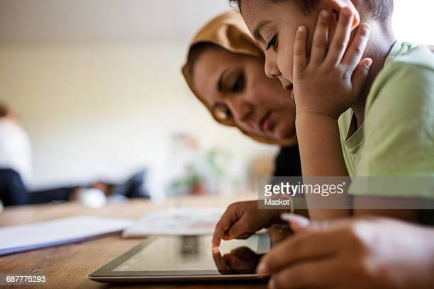 Side view of mother and son using digital tablet while studying at home