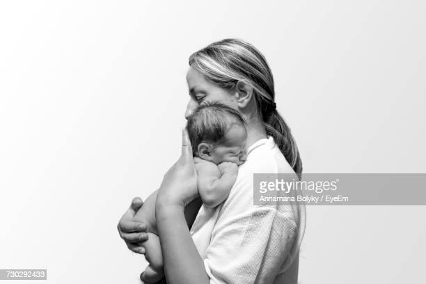 side view of mother carrying naked baby against white background - familia desnuda fotografías e imágenes de stock