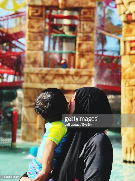 Side View Of Mother Kissing Son At Playground