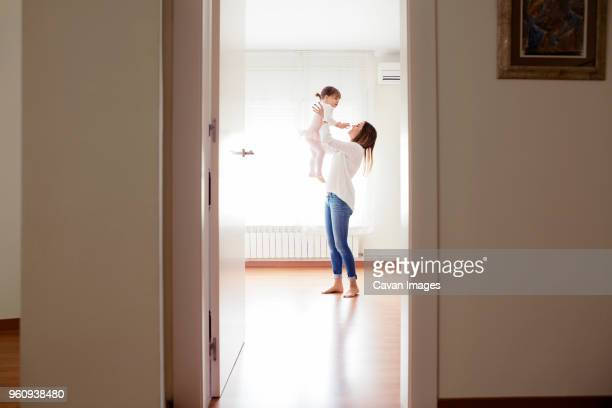 Side view of mother picking girl wearing tutu at home