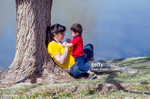 side view of mother sitting with son at lakeshore - by sheldon levis fotografías e imágenes de stock