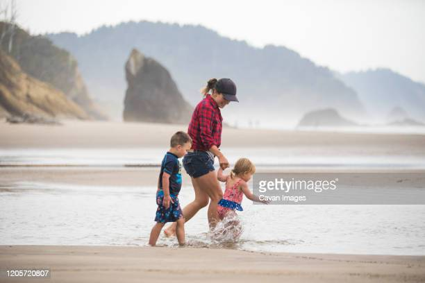 side view of mother walking at beach with her two young kids. - manzanita stock pictures, royalty-free photos & images