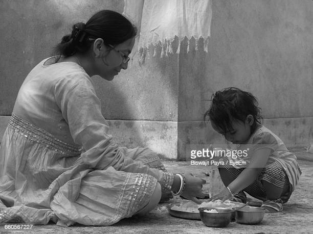 Side View Of Mother With Baby Girl Having Food By Wall
