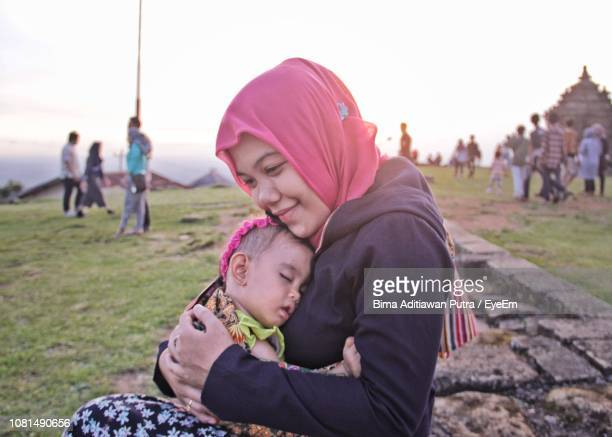 side view of mother with cute sleeping daughter sitting on field against clear sky at park - southeast asia stock pictures, royalty-free photos & images