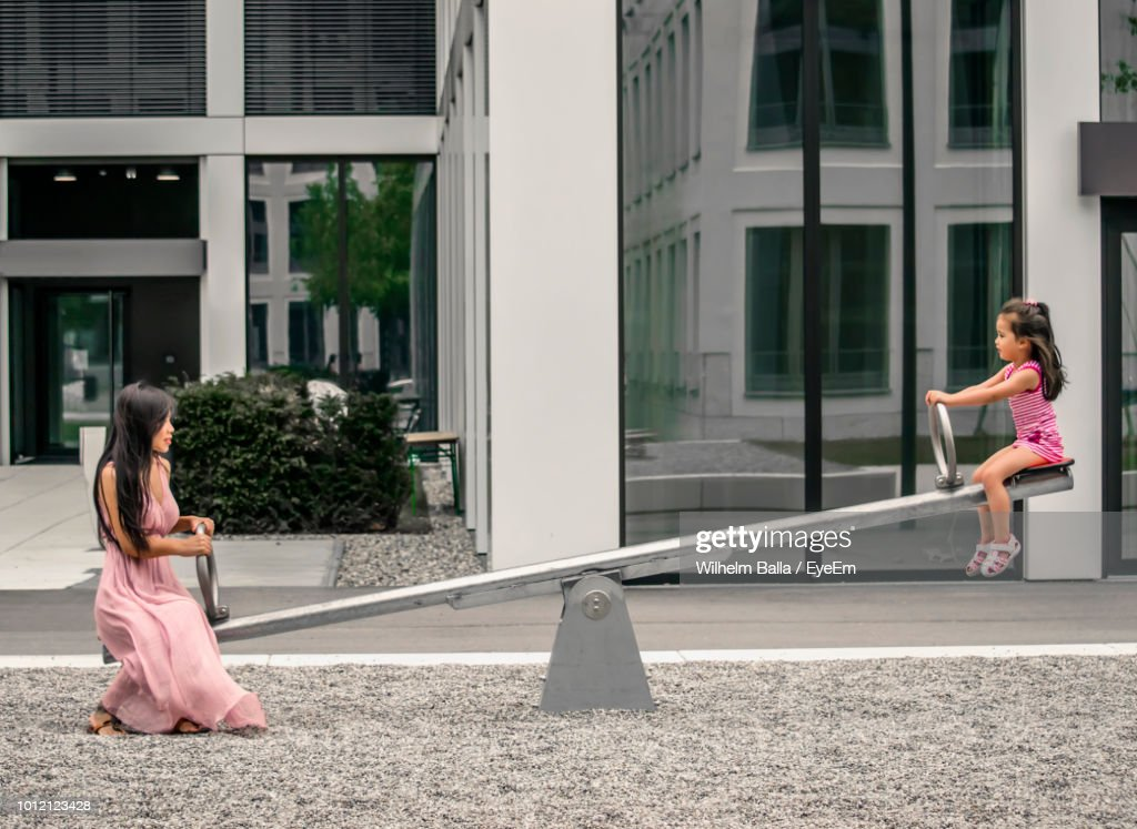 Side View Of Mother With Daughter Playing On Seesaw Against Building : Stock Photo
