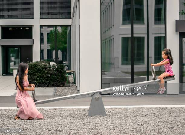 side view of mother with daughter playing on seesaw against building - biciancola foto e immagini stock
