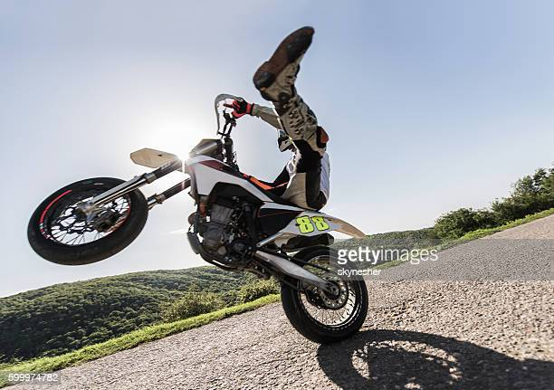 Side view of motorcyclist balancing on front wheel in nature.