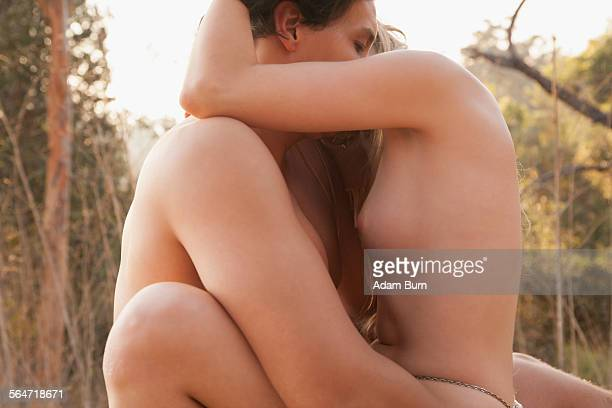 side view of naked couple making love in nature - desnudos femeninos fotografías e imágenes de stock