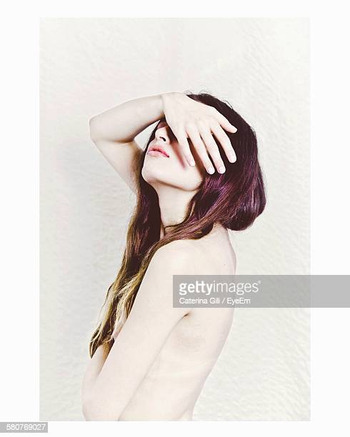 Side View Of Naked Young Woman Covering Face Against White Background