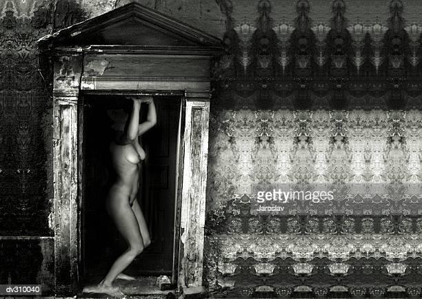 Side view of nude woman in weathered doorway