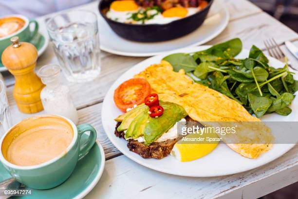 Side view of omlete with avocado toast, spinach salad and coffee cup on the table