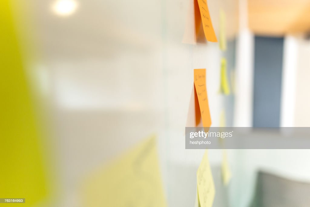 Side view of orange and yellow adhesive notes on whiteboard : Stock Photo