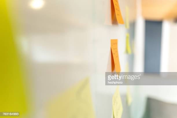 side view of orange and yellow adhesive notes on whiteboard - heshphoto stock pictures, royalty-free photos & images