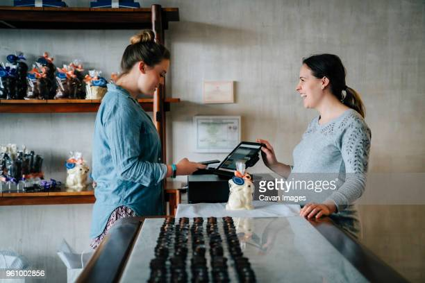 side view of owner laughing while female customer making mobile payment at store - chocolate shop stock pictures, royalty-free photos & images