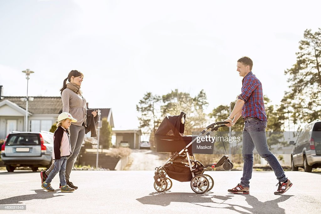 Side view of parents with baby carriage and daughter walking on street : Stock-Foto