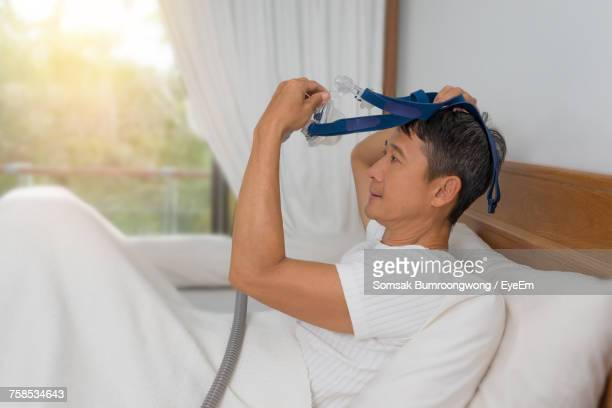 side view of patient wearing oxygen mask while sitting on bed in hospital - respiratory machine stock photos and pictures