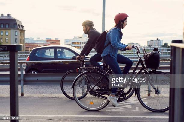 side view of people cycling on street against sky - cycle vehicle stock photos and pictures