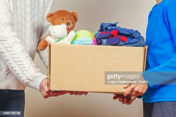 side view of people holding box filled with toys - charitable donation stock pictures, royalty-free photos & images