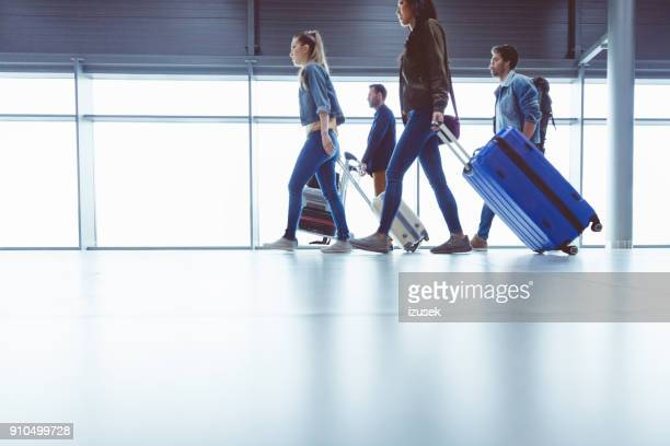 side view of people walking with suitcase at airport terminal - airport terminal stock photos and pictures