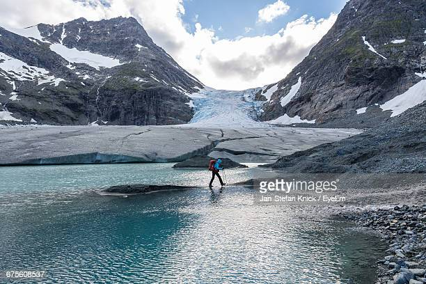 side view of person hiking at glacier lake against mountains - glacier lagoon stock photos and pictures