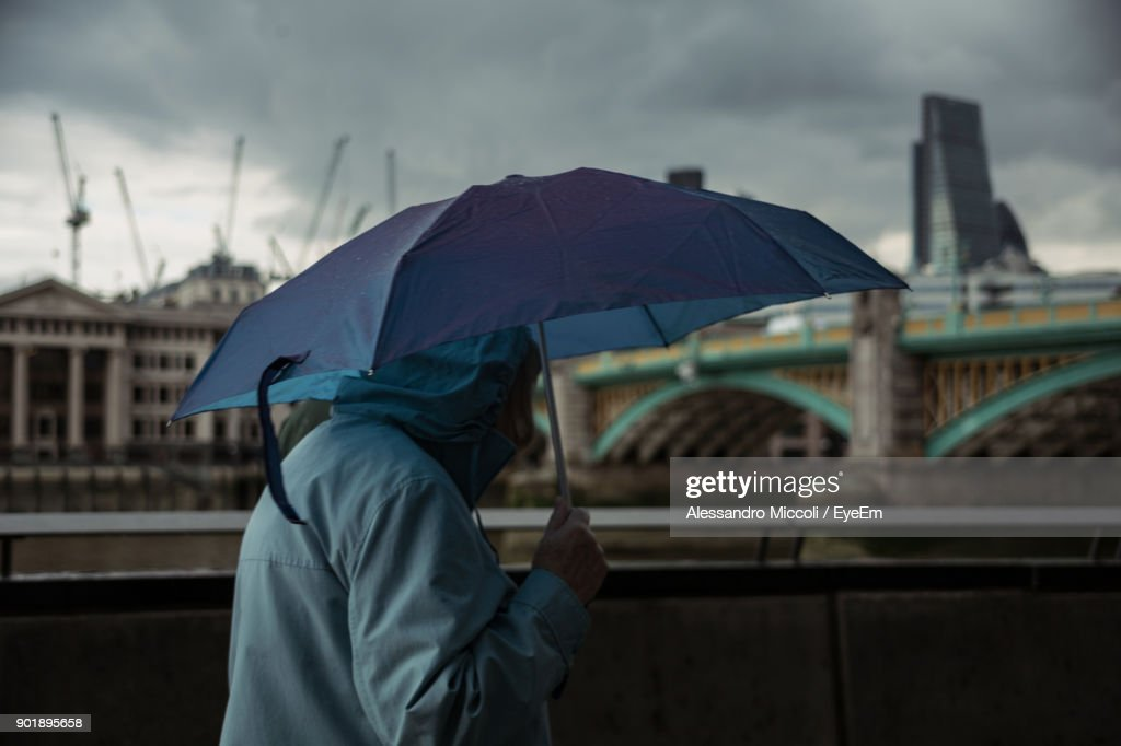 Side View Of Person Holding Umbrella While Walking In City : Stock Photo