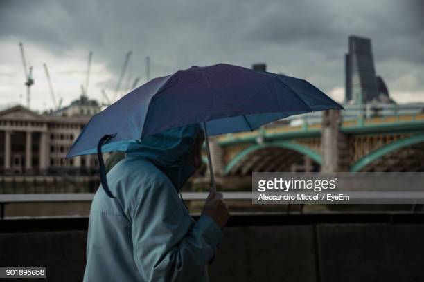side view of person holding umbrella while walking in city - alessandro miccoli stock photos and pictures
