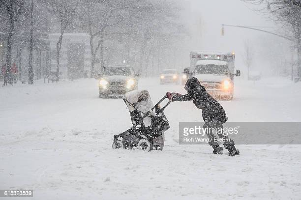 Side View Of Person Pushing Baby Carriage On Street During Snowfall