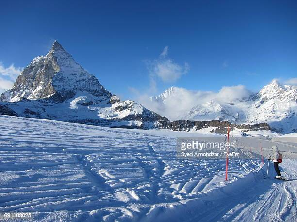 Side View Of Person Skiing On Snowfield Against Sky