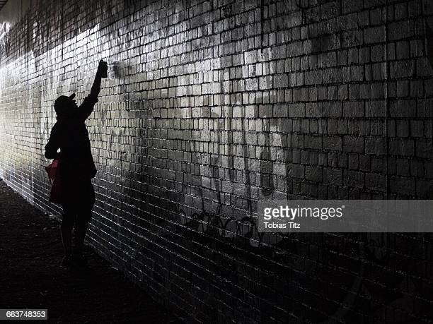 Side view of person spray painting on wall