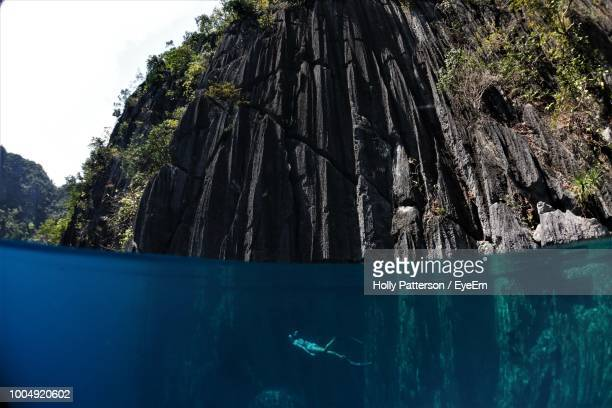 side view of person swimming undersea - el nido stock pictures, royalty-free photos & images