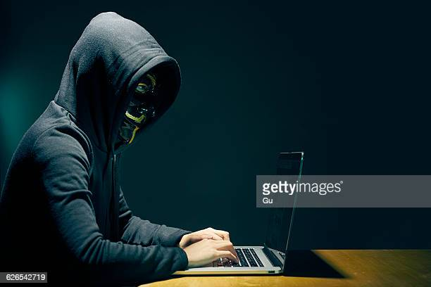 Side view of person wearing hooded top and Guy Fawkes face mask using laptop