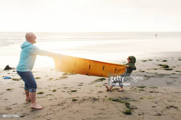 Side view of playful father and son pulling picnic blanket at beach against clear sky