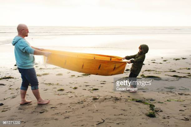 Side view of playful father and son pulling picnic blanket while standing on shore at beach against clear sky