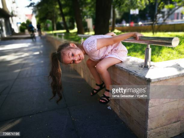 Side View Of Playful Girl Sitting On Retaining Wall By Footpath