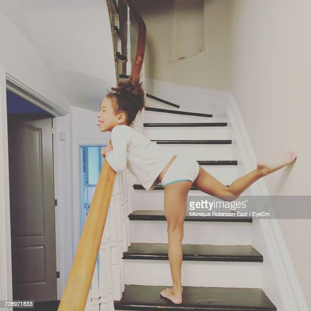 Side View Of Playful Girl Sticking Out Tongue While Standing On Steps At Home