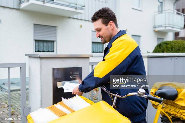 side view of postal worker inserting letters in mailbox - postal worker stock pictures, royalty-free photos & images