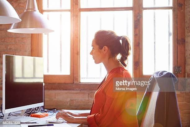 Side view of pregnant businesswoman using computer