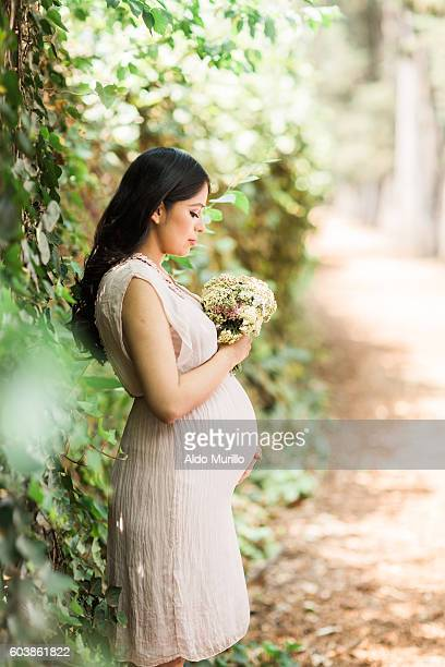 Side view of pregnant woman holding a bouquet