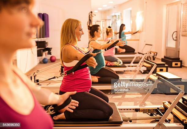Side view of pregnant women exercising on Pilates machine.