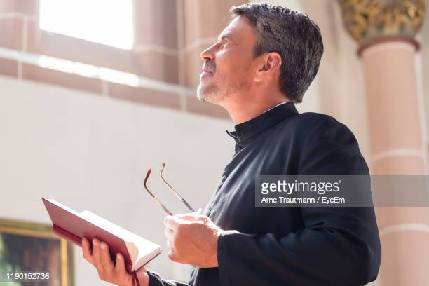 side view of priest looking away while holding bible - catholicism stock pictures, royalty-free photos & images
