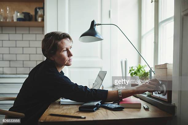side view of product designer adjusting radio at home office - radio foto e immagini stock
