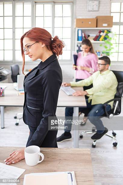 Side view of redhead office worker posing in workplace