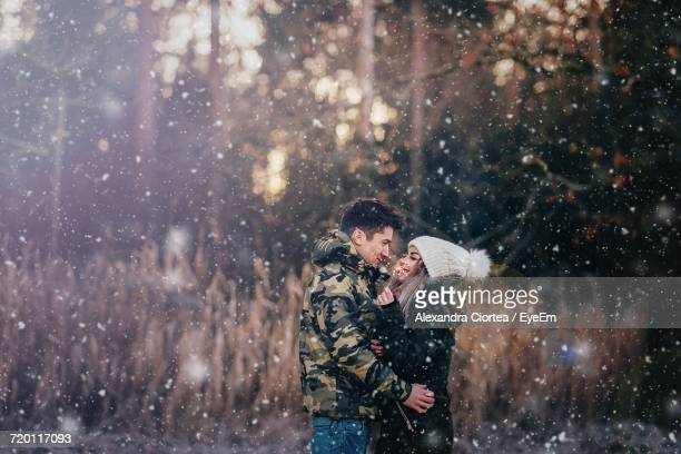 Side View Of Romantic Couple Standing At Forest During Snowfall
