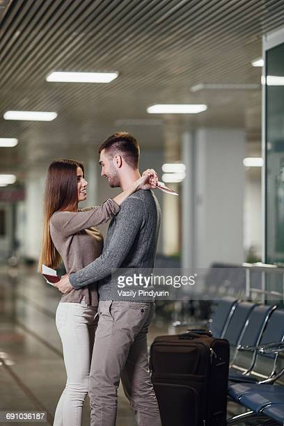Side view of romantic young couple embracing at airport