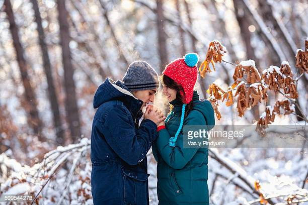 Side view of romantic young couple holding hands during winter