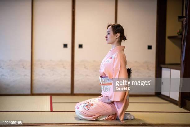 和室でヒールに座っている着物のロシア人女性の側面図 - 着物 ストックフォトと画像