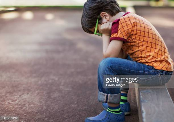 side view of sad boy wearing eyeglasses sitting on curb by footpath - curb stock pictures, royalty-free photos & images