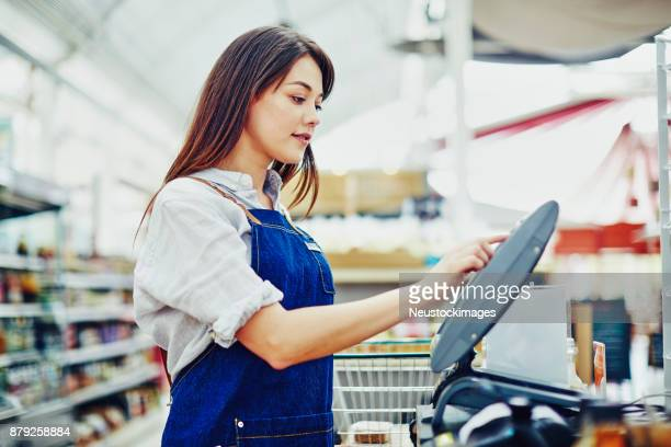 side view of saleswoman using cash register in delicatessen - convenience store stock photos and pictures