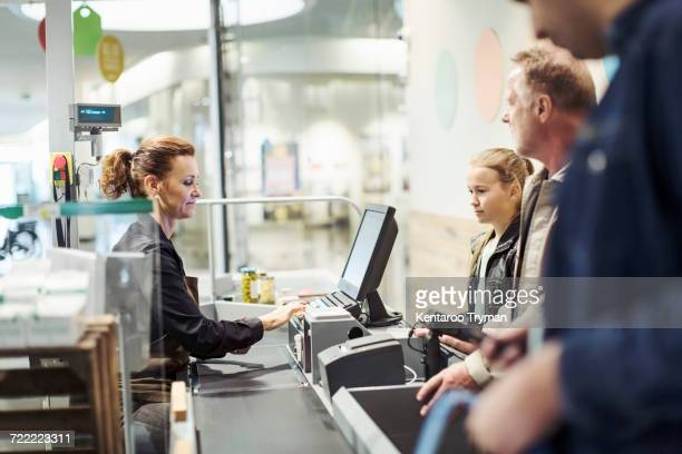 Side view of saleswoman using computer while customer standing at checkout counter in supermarket
